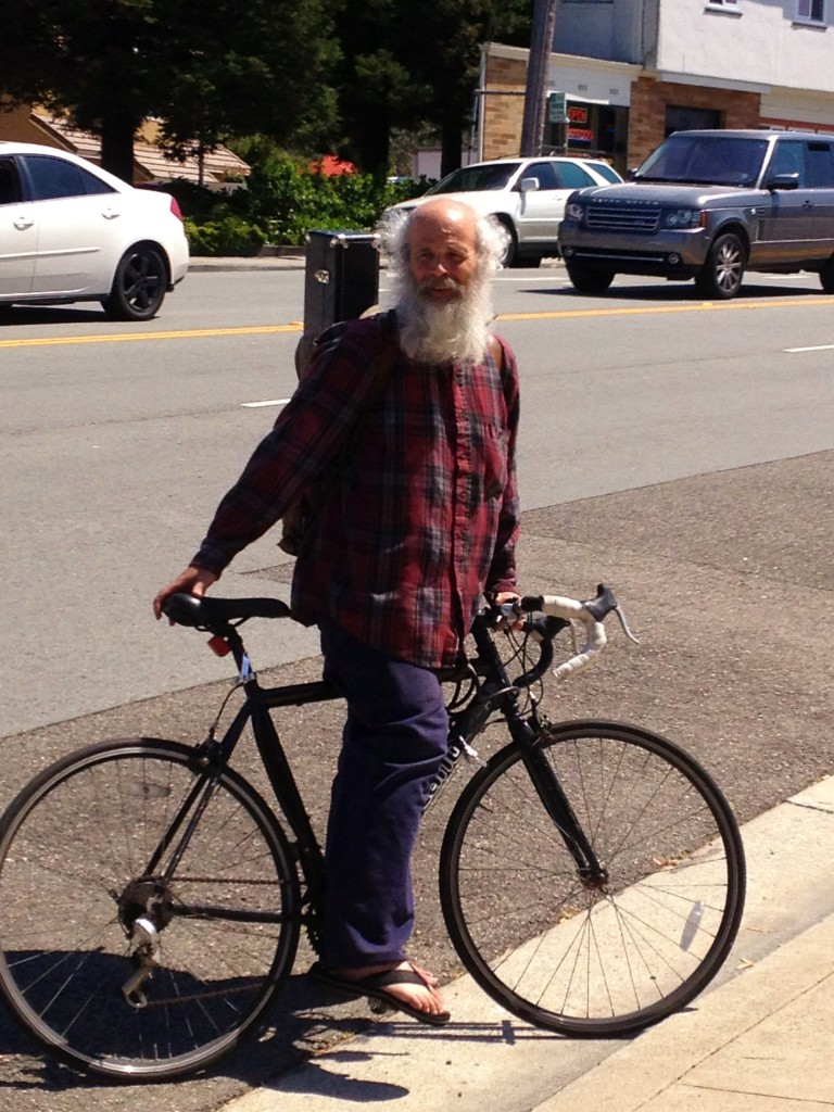 Greybeard cyclist off to saxaphone cyclist